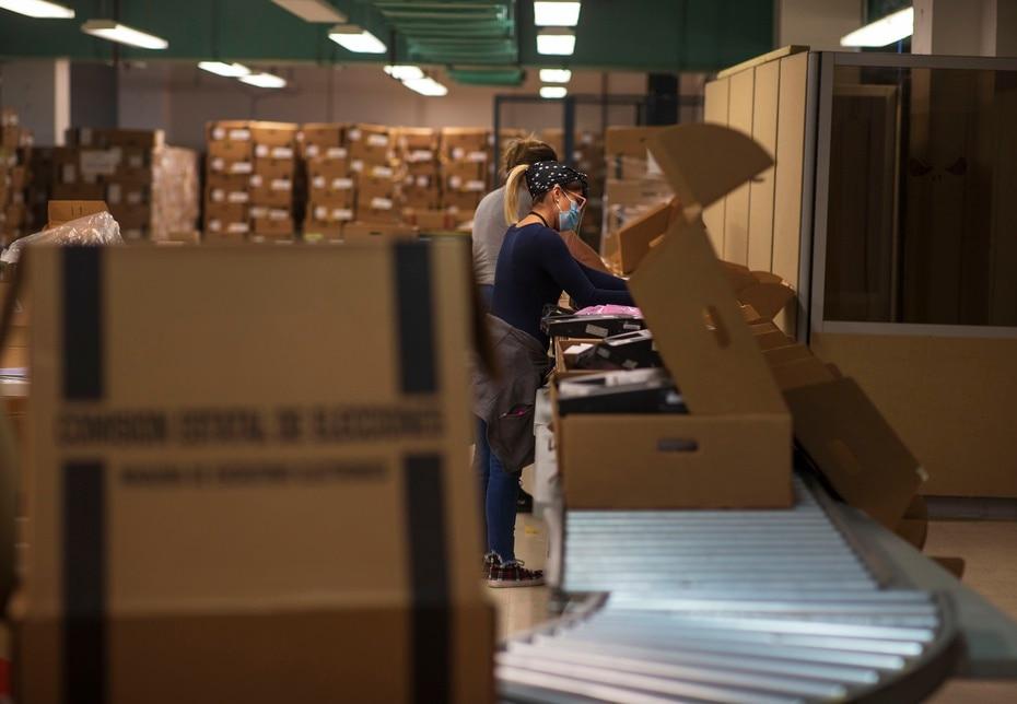 En la foto, funcionarios trabajan en el mantenimiento de las máquinas de escrutinio.