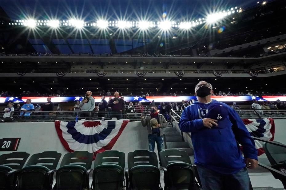 Fanáticos en el Globe Life Field escuchan el himno nacional previo al cuarto partido de la Serie Mundial.