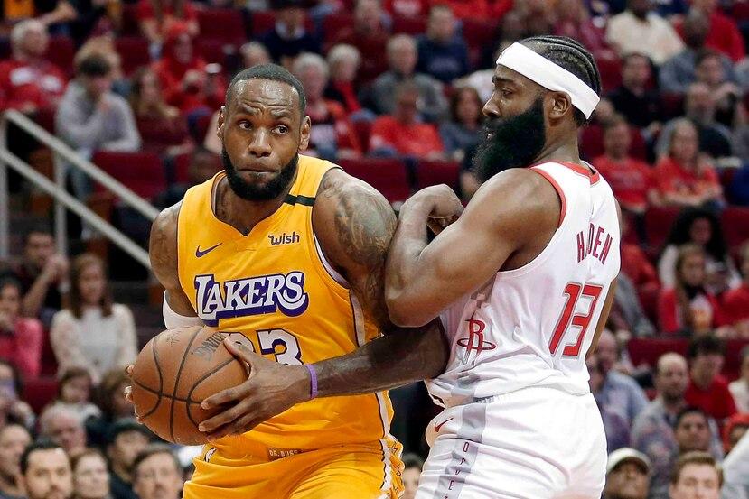 LeBron James intenta penetrar al canasto ante la defensa de James Harden. (AP)