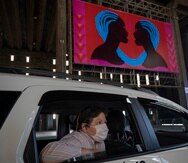 Una mujer con una mascarilla para protegerse del coronavirus observa una exposición artística desde un automóvil el viernes 24 de julio de 2020, en una nave donde están expuestas pinturas y fotografías, en Sao Paulo, Brasil. (AP Foto/André Penner)