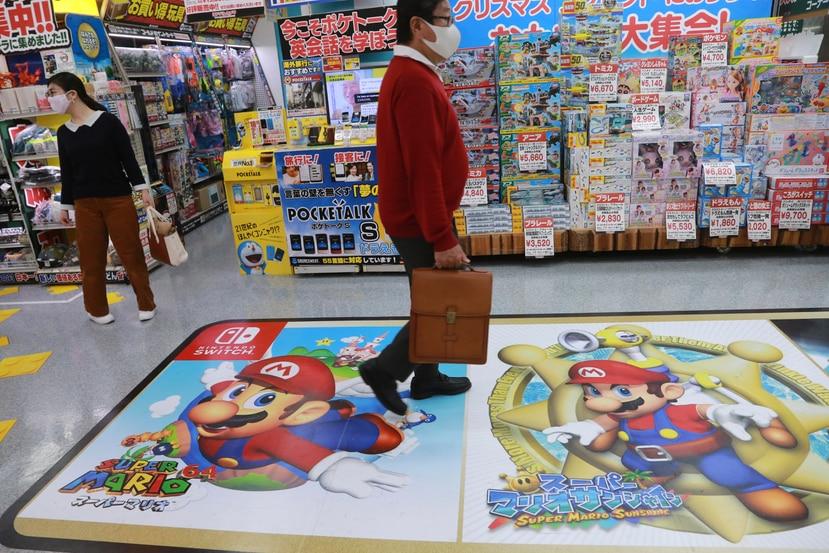 Un comprador pasa por encima de un anuncio de Super Mario, de Nintendo, en una tienda de electrónica en Tokio.