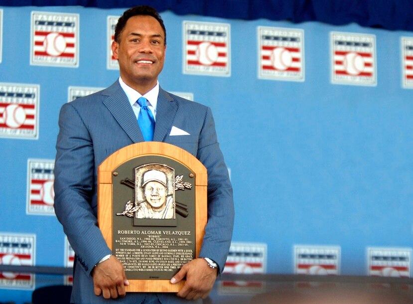Roberto Alomar sostiene su placa del Salón de la Fama de Béisbol durante su exaltación en 2011.