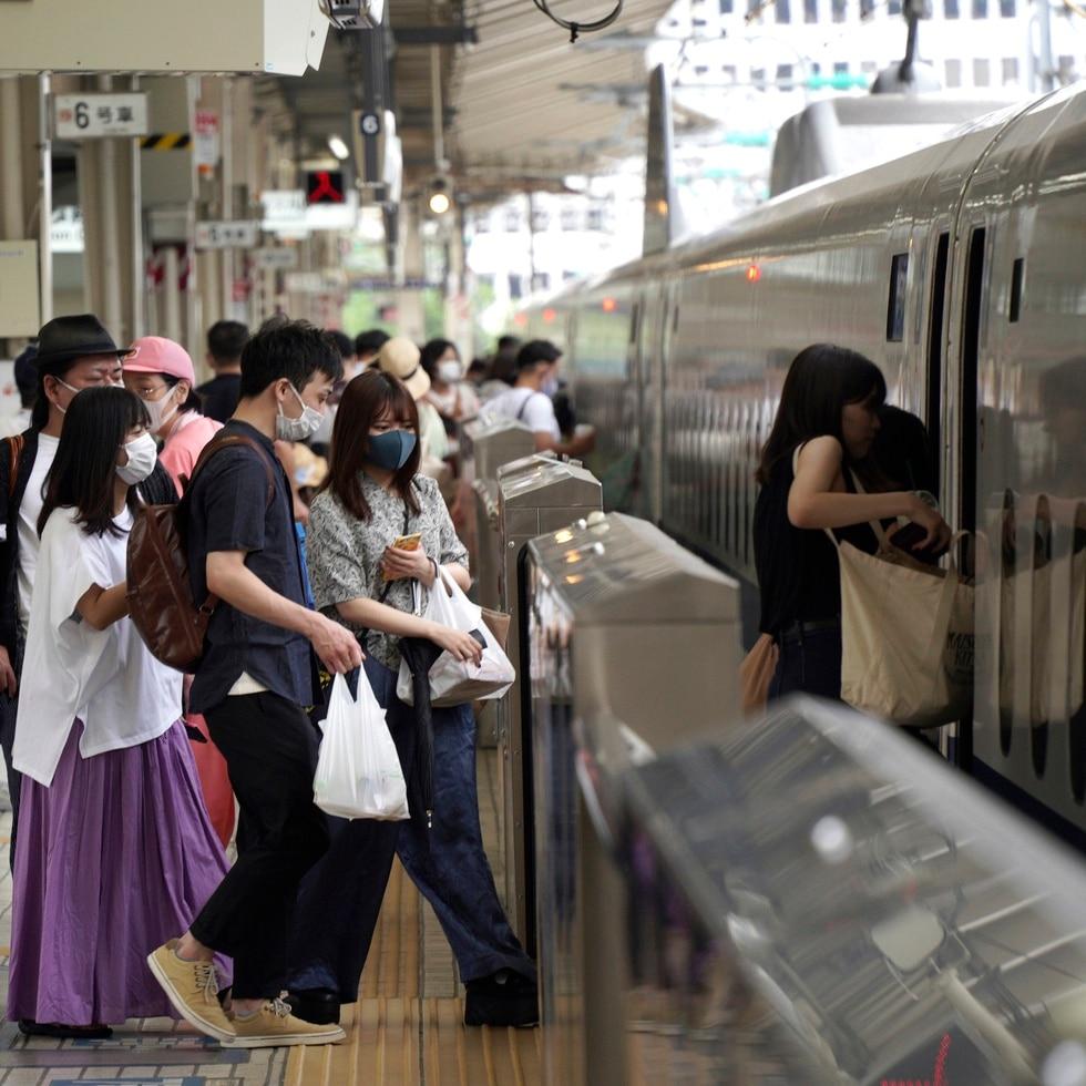 Japoneses abordan un tren bala.