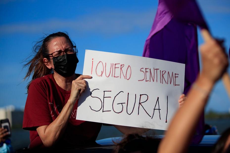 """Una manifestante con su pancarta y el mensaje """"quiero sentirme segura""""."""