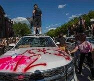 Manifestantes vandalizan un vehículo del Servicio Secreto frente a la Casa Blanca. (AP)