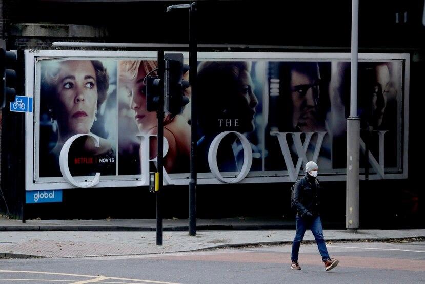 "Un hombre pasa frente a un anuncio de la serie de Netflix ""The Crown"" en Londres."
