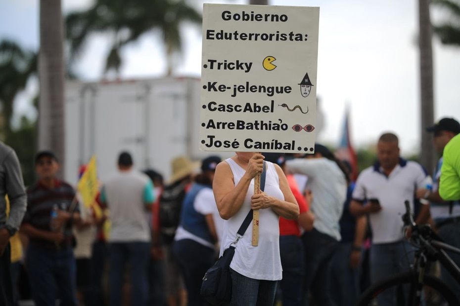 Una mujer porta una pancarta que tilda a varios políticos y jefes de agencias de terroristas.