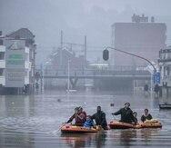 Residentes usan balsas inflables para navegar la crecida luego que el río Meuse se desbordó debido a fuertes aguaceros en Lieja, Bélgica, el 15 de julio del 2021.  (AP Foto/Valentin Bianchi)