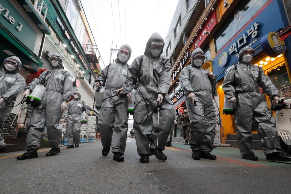 Soldados del ejército de Corea del Sur con equipo de protección rocían desinfectante como precaución contra el nuevo coronavirus en una calle comercial en Seúl, Corea del Sur, el miércoles 4 de marzo de 2020. La epidemia de coronavirus se desplazó cada vez más hacia el oeste, hacia el Medio Oriente, Europa y Estados Unidos.