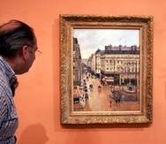 """Un visitante observa el cuadro impresionista """"Rue St.-Honore, Apres-Midi, Effet de Pluie"""" pintado en 1897 por Camille Pissarro, expuesto en el Museo Thyssen-Bornemisza, en Madrid."""