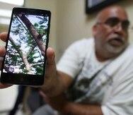 Pedro Juan Cotto Pérez, residente de Toíta, muestra una imagen del tendido eléctrico.