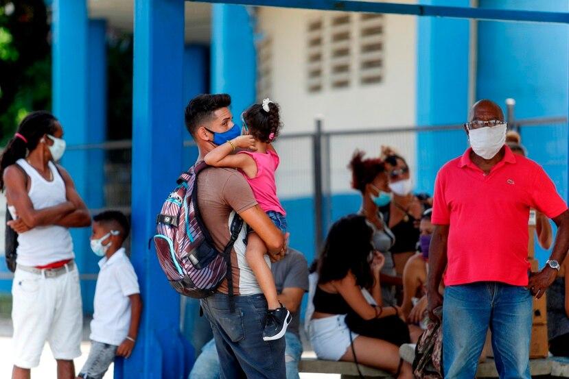 Varias personas esperan en una parada de autobus, en La Habana (Cuba).