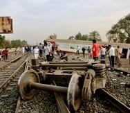 Unas personas observan los restos de un tren descarrilado cerca de Banha, en Egipto.