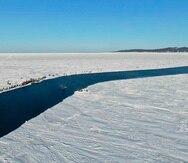 Un grupo de pescadores usan un pequeño trozo de hielo como balsa para llegar remando a la costa. (Servicio de prensa Ministerio de Emergencias de Rusia vía AP)