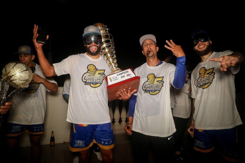 Javier Mojica, el dirigente Nelson Colón y Benito Santiago Jr. posan con el trofeo de campeonato.