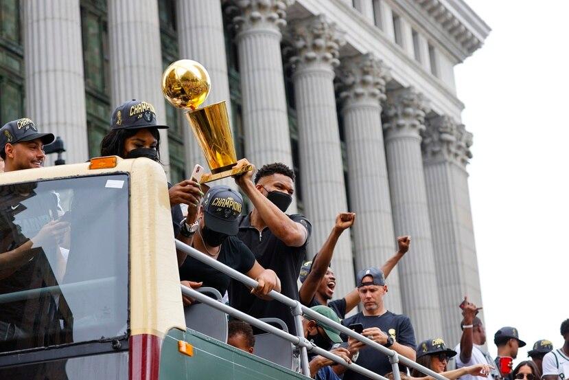 Giannis Antetokounmpo alza el trofeo de campeonato de la NBA durante la parada d los Bucks en la ciudad de Milwaukee.