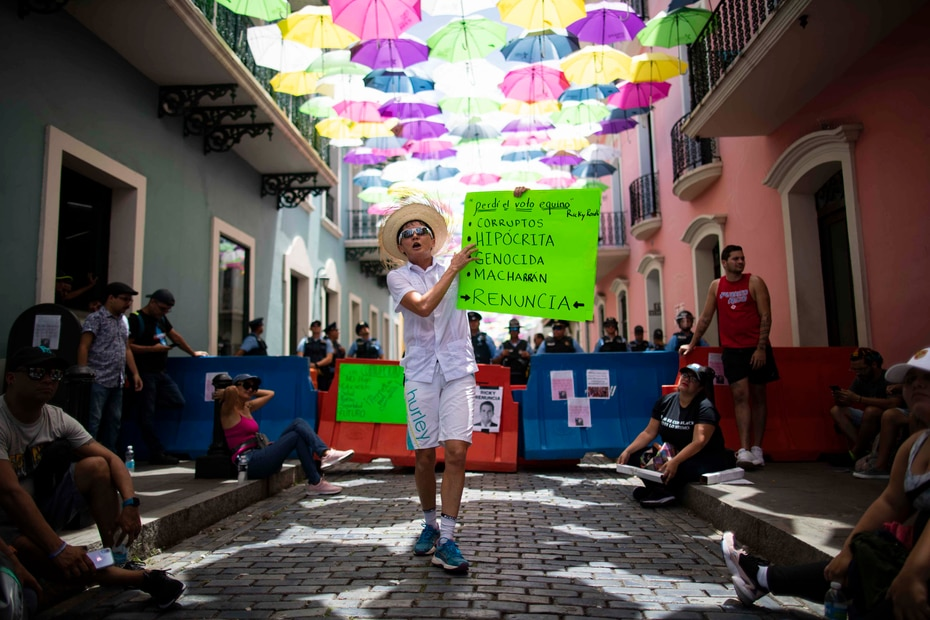 Manifestante carga con una pancarta que pide la renuncia al gobernador.