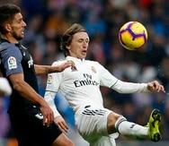 Luka Modric pelea por el control del balón contra Daniel Carrico. (AP)