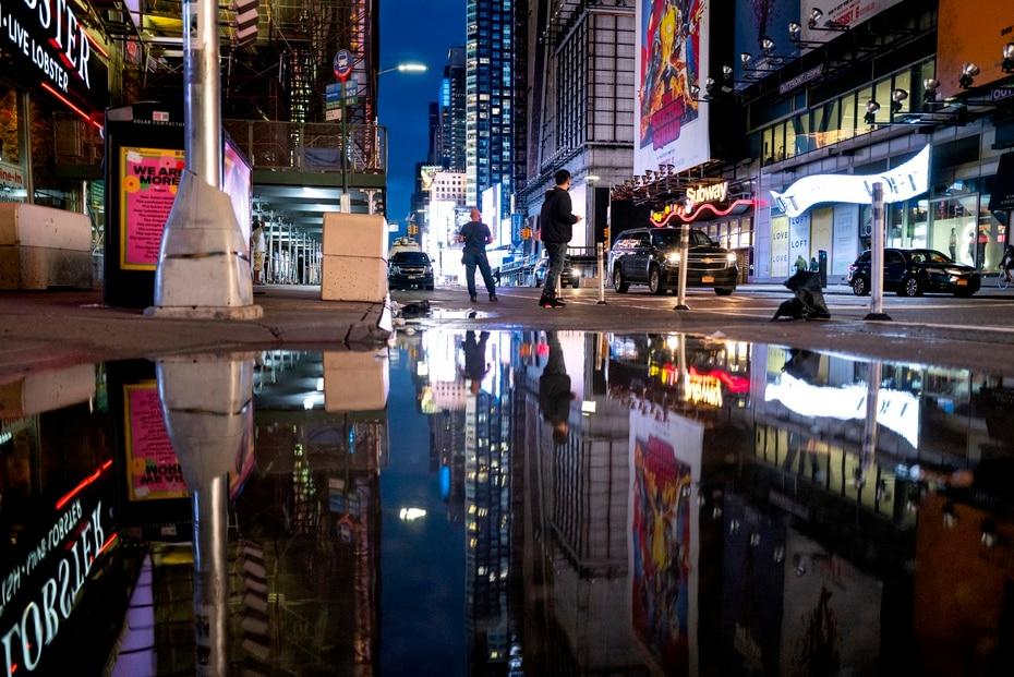 Las imágenes de las pantallas en Times Square se reflejan en los charcos de agua provocado por las inundaciones.