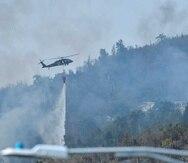 Helicóptero de la Guardia Nacional echa agua en el área del fuego forestal en Gurabo.