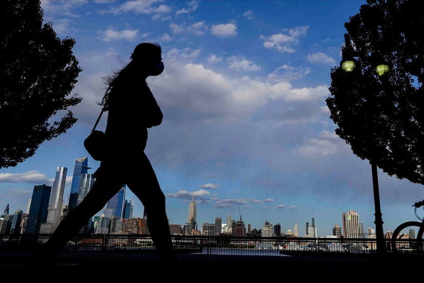 Una mujer con mascarilla camina por Sinatra Drive North con vista al centro de Manhattan. (AP)