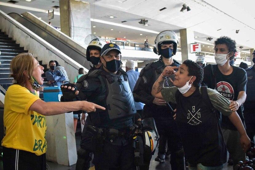 Oficiales de la policía militar brasileña separan a los manifestantes leales al presidente de Brasil, Jair Bolsonaro, y a los manifestantes antigubernamentales, justo después de una protesta contra el racismo. (AP)