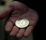 Un hombre sujeta un Bitcoin.