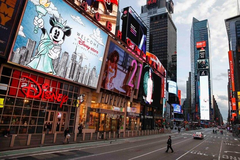 Un policía cruza una séptima avenida vacía en un Times Square escasamente poblado debido al temor a contagio de COVID-19, la tarde del viernes 20 de marzo de 2020, en Nueva York. (AP/John Minchillo)