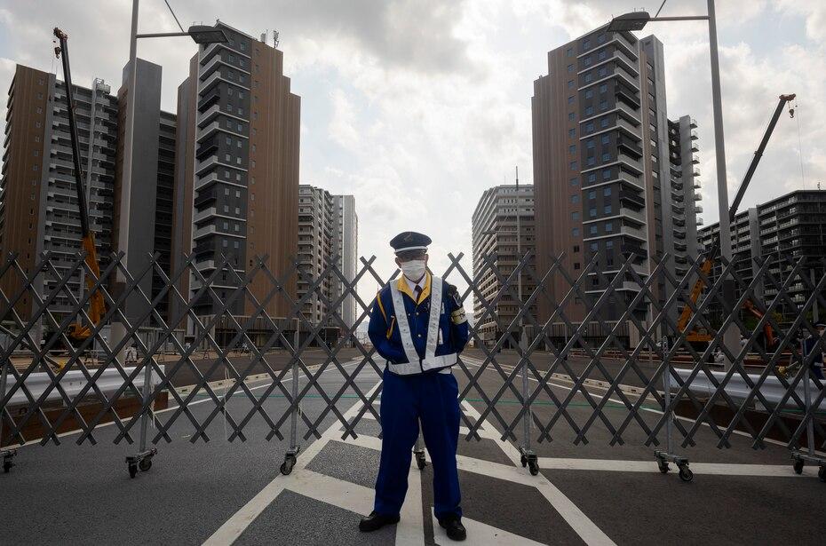 Un guardia de seguridad frente a un valla protectora en la Villa de Atletas de los pospuestos Juegos Olímpicos de Tokio 2020, el jueves 8 de abril de 2021. (AP Foto/Hiro Komae)