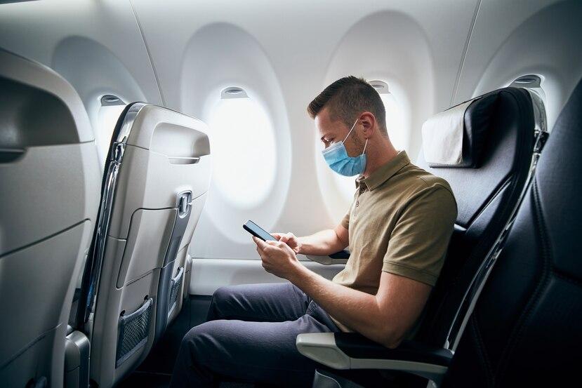 Un hombre utiliza mascarilla mientras está en el interior de un avión.