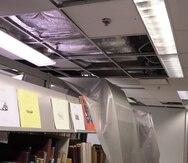 La foto muestra estantes con libros cuya única protección del agua y sucio generado por el sistema de aire acondicionado en el techo expuesto son pedazos de tela de plástico.