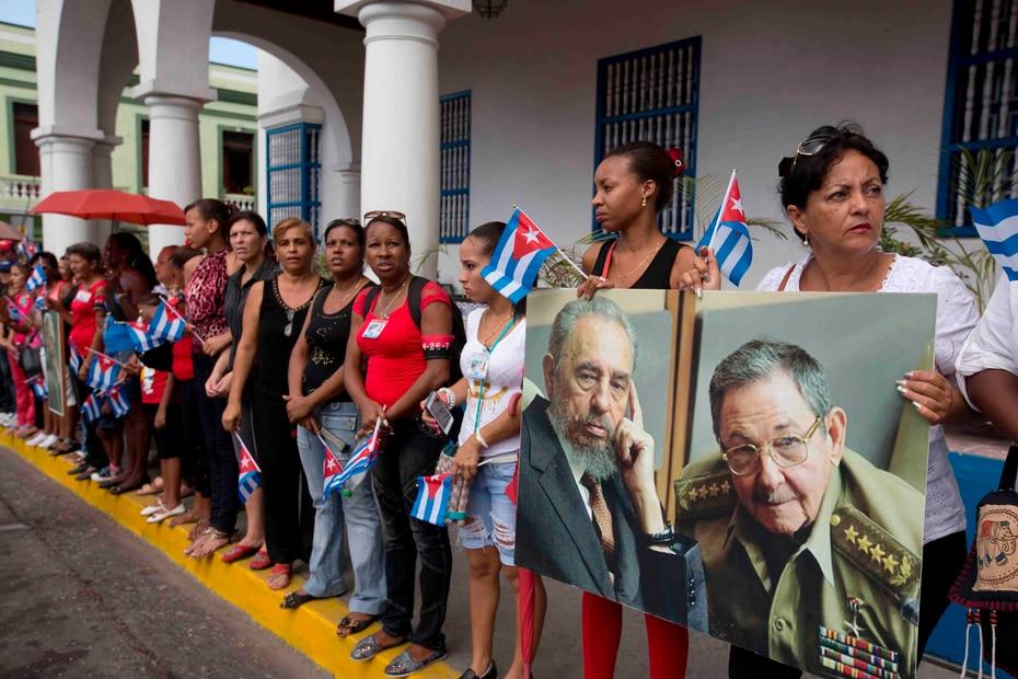 El 3 de diciembre de 2016 las mujeres retratan al difunto Fidel Castro y al presidente Raúl Castro mientras esperan ver la llegada de la caravana que transporta las cenizas del líder cubano.