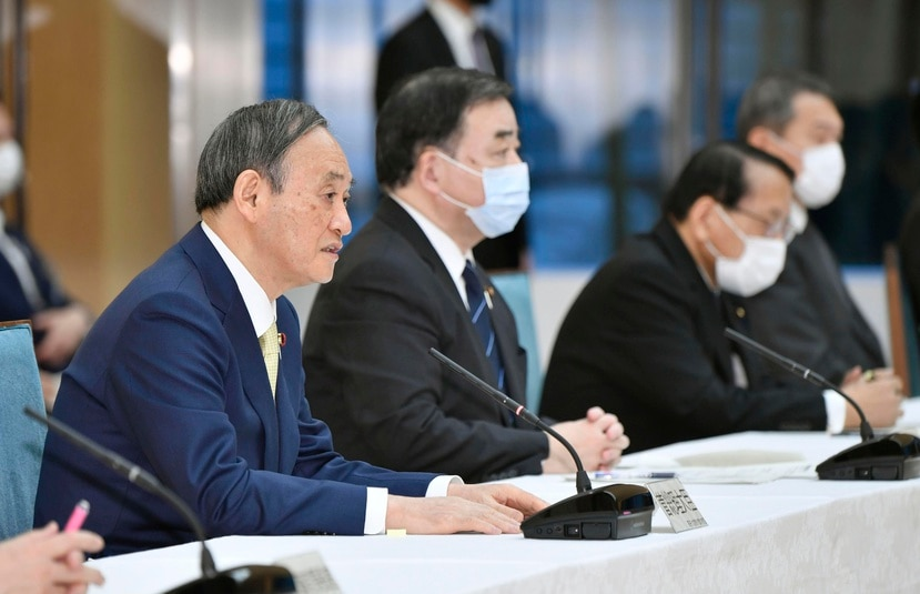 El primer ministro japonés Yoshihide Suga, izquierda, participa en una reunión de gabinete.