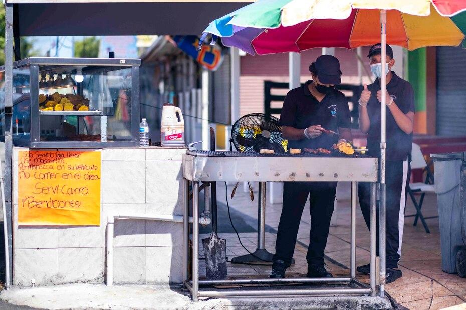 Dos jóvenes hacen pinchos en un negocio en Piñones.