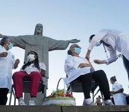 Terezinhah da Conceicao, de 80 años (izq) y Dulcinea da Silva Lopes, de 59, reciben la vacuna china contra el COVID-19 de Sinovac el 18 de enero del 2021 en Río de Janeiro, con el Cristo Redentor de fondo. Fueron las dos primeras brasileñas en inocularse contra el coronavirus con la vacuna china. (AP Photo/Bruna Prado, File)