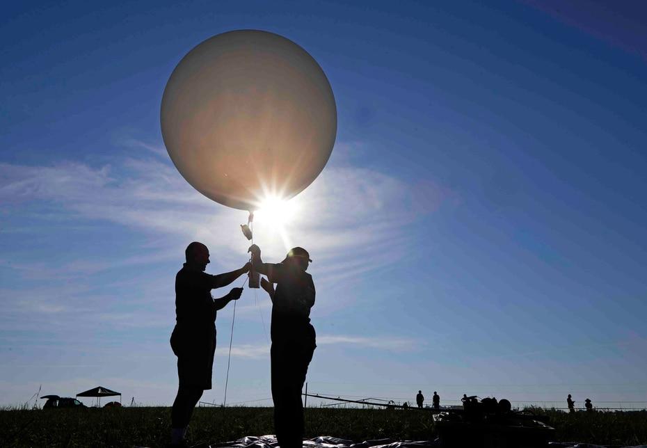 El profesor de química atmosférica de la Universidad de Alabama en Huntsville, Mike Newchurch, y la estudiante graduada Paula Tucker preparan el globo atmosférico que lanzarán durante el eclipse para realizar investigaciones. (The Associated Press)