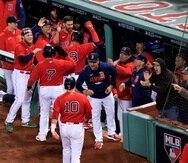 El dirigente de los Red Sox, Alex Cora, recibe a sus jugadores en el dugout luego de gran slam de Kyle Schwarber en la segunda entrada.