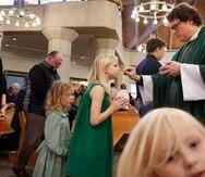 El reverendo Joshua Withfield toma la comunión a su esposa Alli y a las hijas de ambos Zoe-Catherine (izq), y Maggie en la iglesia Santa Rita de Dallas. (AP)