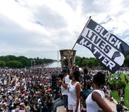 """A woman holds a """"Black Lives Matter,"""" flag during the March on Washington, Friday Aug. 28, 2020, at the Lincoln Memorial in Washington, on the 57th anniversary of the Rev. Martin Luther King Jr.'s """"I Have A Dream"""" speech. (AP Photo/Alex Brandon)"""