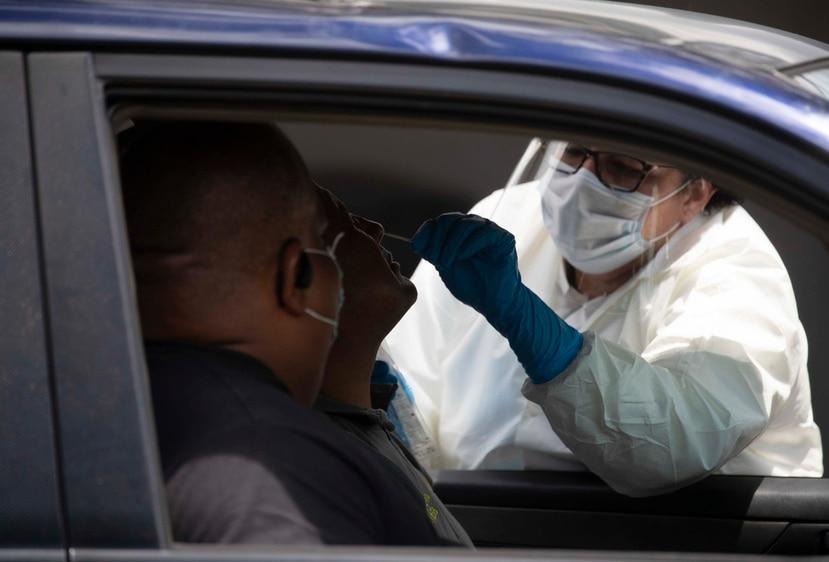 Personal médico toma una muestra para una prueba molecular en un laboratorio servicarro en San Juan.