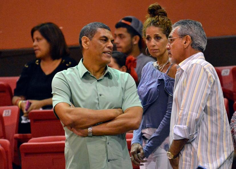 Raymond Dalmau (izq.) y su esposa, Sandra, conversan con Oscar Hernández en un partido de los Piratas de Quebradillas. (GFR Media)