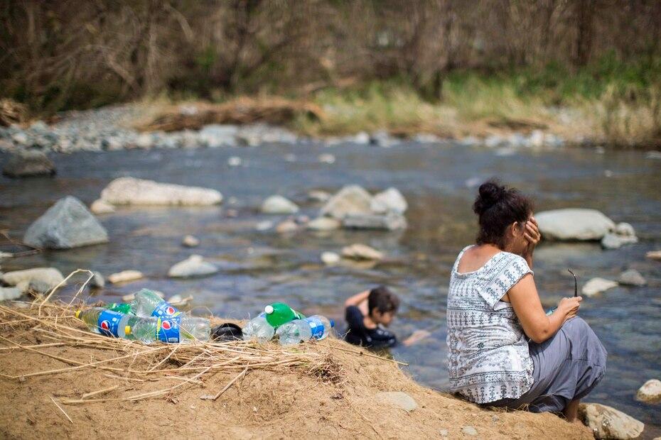 Nancy González espera a que sus hijos se refresquen en el río, luego de recoger agua en unos envases.