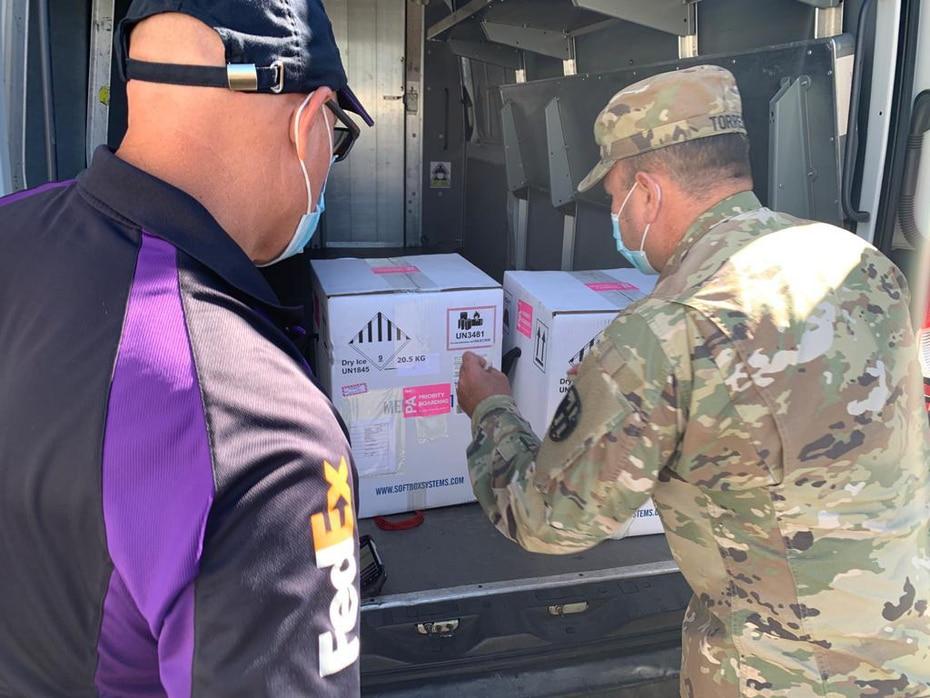 Un empleado de Fedex, la compañía que trasladó las vacunas desde Estados Unidos a Puerto Rico, observa a un efectivo de la Guardia Nacional colocar las cajas con las vacunas en la parte trasera de un vehículo.