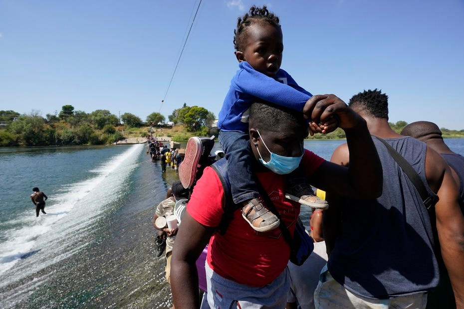 Los migrantes caminaron sobre una represa, con el agua llegándole a los pies, por lo que tuvieron que cargar a bebés y niños en sus espaldas para cruzar al otro lado.
