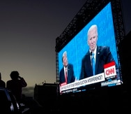 People watch from their vehicle as President Donald Trump, on left of video screen, and Democratic presidential candidate former Vice President Joe Biden speak during a Presidential Debate Watch Party at Fort Mason Center in San Francisco, Thursday, Oct. 22, 2020. The debate party was organized by Manny's, a San Francisco community meeting and learning place. (AP Photo/Jeff Chiu)