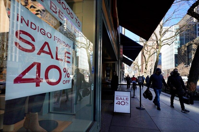 Compradores pasan frente a una tienda que ofrece descuentos hasta de 40%, en el famoso distrito comercial Magnificent Mile en Chicago, el sábado 28 de noviembre de 2020.