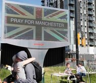 Foto de archivo, 23 de mayo de 2017, de una pareja abrazada bajo un cartel en Manchester, Inglaterra, al día siguiente de un ataque suicida en un concierto de Ariana Grande que dejó más de 20 muertos en la Manchester Arena. (AP Foto/Kirsty Wigglesworth, F