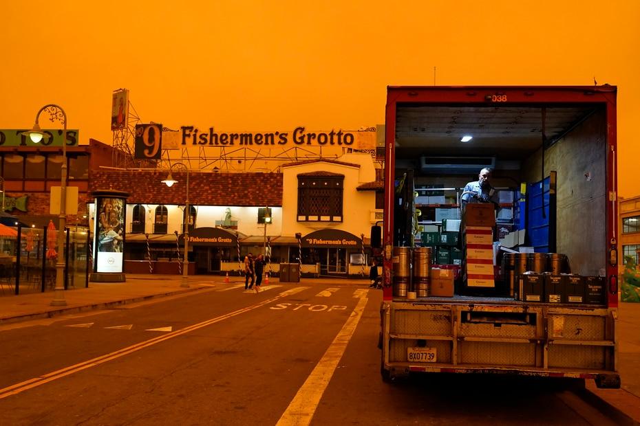Un conductor descarga licor en el barrio californiano Fisherman's Wharf bajo el cielo oscurecido por el humo.