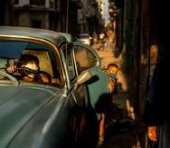 Un niño juega cerca de un carro viejo en la Habana Vieja, Cuba.