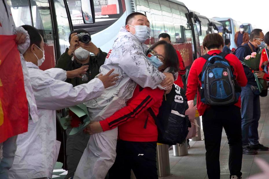 Una trabajadora médica de la provincia china de Jilin, de rojo, abraza a un compañero de Wuhan mientras se prepara para regresar a su casa desde el aeropuerto internacional Wuhan Tianhe, en Wuhan, China.